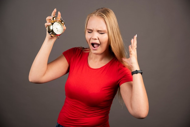 Jeune femme avec horloge ayant une panne.