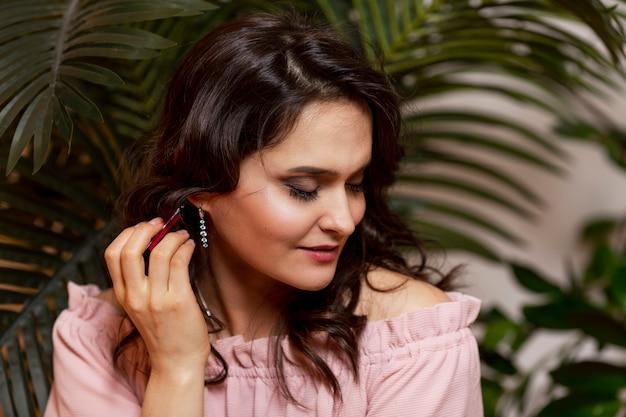 Jeune femme avec de l'huile aromatique à la main. profitez du parfum de la nature. belle brune dans un pull rose.