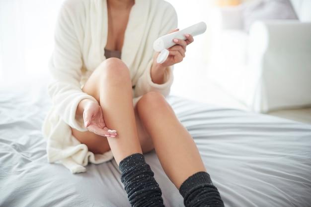 Jeune femme hydratant ses jambes