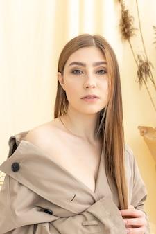 Jeune femme en imperméable beige avec épaule nue sur fond de tissu pastel