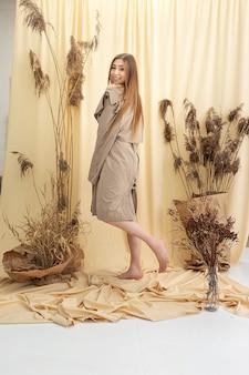 Jeune femme en imperméable beige sur fond de tissu pastel