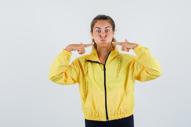 Jeune femme en imperméable jaune pointant sur ses joues gonflées
