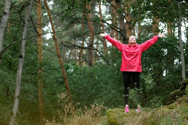 Jeune femme en imperméable rose, faire des exercices de yoga en forêt.