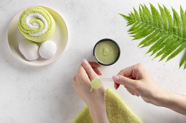 Jeune femme impose un gommage avec une cuillère à la main. concept de soins du corps. mur blanc avec feuille verte et serviette de bain. mise à plat. place pour le texte