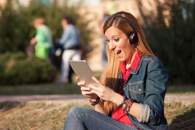 Jeune femme impressionnée et excitée en écoutant de la musique sur la tablette