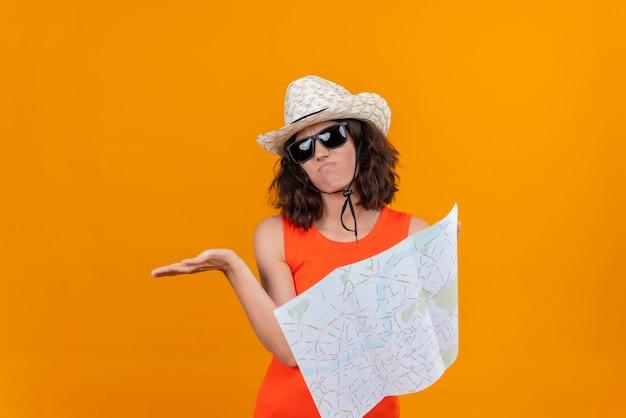 Une jeune femme impuissante aux cheveux courts dans une chemise orange portant un chapeau et des lunettes de soleil tenant une carte