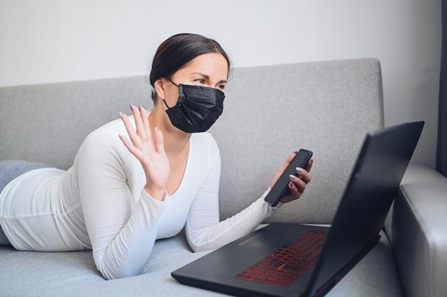 Jeune femme indépendante dans le masque de médecine du visage pour effectuer un appel vidéo avec un ordinateur portable sur un canapé gris pendant la mise en quarantaine à domicile de l'isolement des coronavirus. virus corona pandémique covid-19. travail en ligne depuis le concept de la maison.