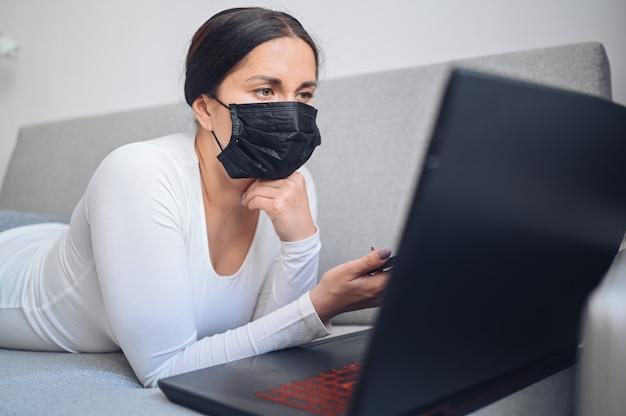 Jeune femme indépendante dans le masque de médecine du visage travaillant sur un ordinateur portable et un téléphone sur un canapé gris pendant la mise en quarantaine à domicile de l'isolement des coronavirus. virus corona pandémique covid-19. travail en ligne depuis le concept de la maison.