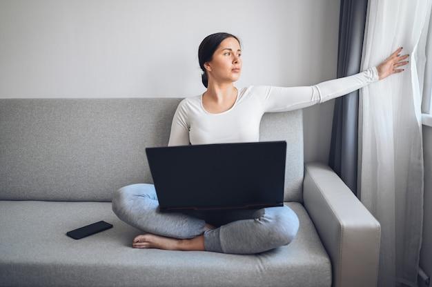 Jeune femme indépendante européenne travaillant sur un ordinateur portable et un téléphone sur un canapé gris pendant la mise en quarantaine à domicile de l'isolement des coronavirus. virus corona pandémique covid-19. travail en ligne à distance du concept de la maison.
