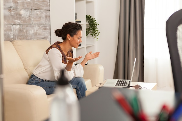 Jeune femme indépendante souriante lors d'un appel vidéo sur ordinateur portable travaillant à domicile.