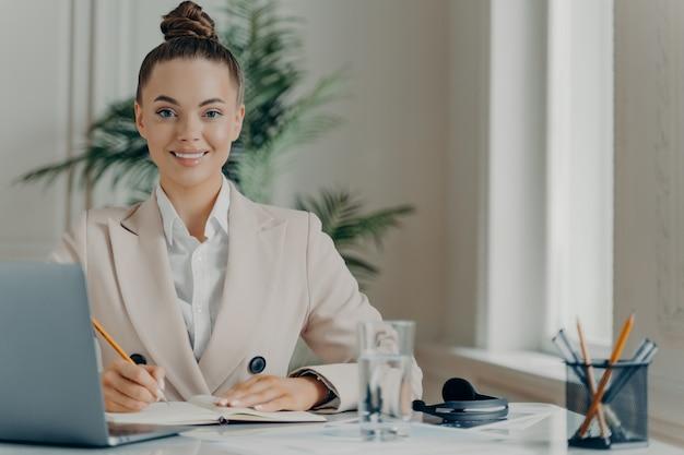 Jeune femme indépendante à succès appréciant le travail à distance, femme d'affaires positive assise au bureau et travaillant sur un ordinateur portable, notant des informations dans le bloc-notes et souriant joyeusement à la caméra