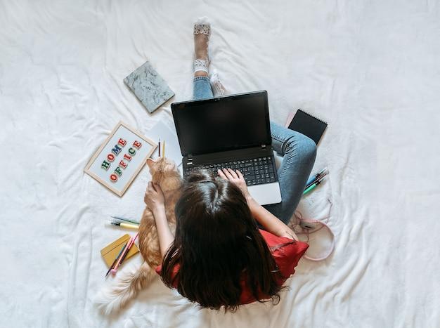 Jeune femme indépendante travaillant dans un bureau à domicile avec un ordinateur portable et un chat travaillant en ligne à distance