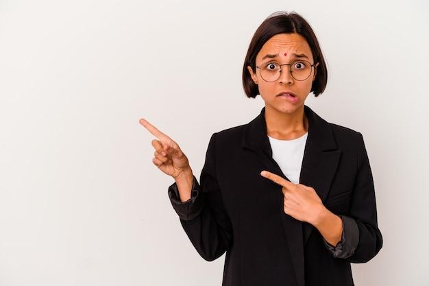 Jeune femme indienne d'affaires isolé sur fond blanc choqué de pointer avec l'index vers un espace de copie.