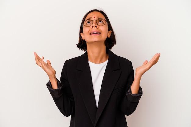 Jeune femme indienne d'affaires isolé sur fond blanc criant vers le ciel, levant les yeux, frustré.