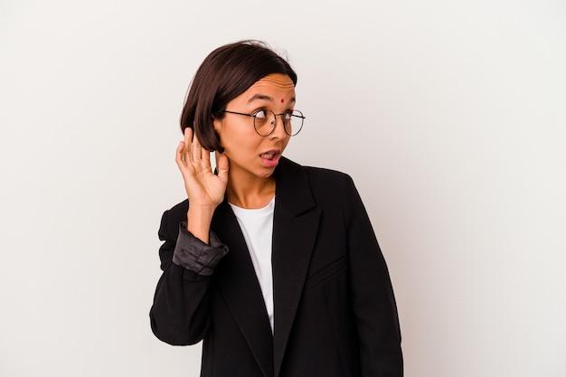 Jeune femme indienne d'affaires isolé sur fond blanc essayant d'écouter un potin.