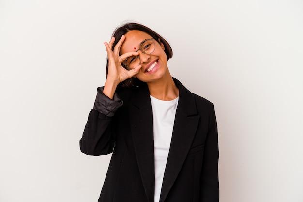 Jeune femme indienne d'affaires isolé sur fond blanc excité en gardant le geste ok sur les yeux.