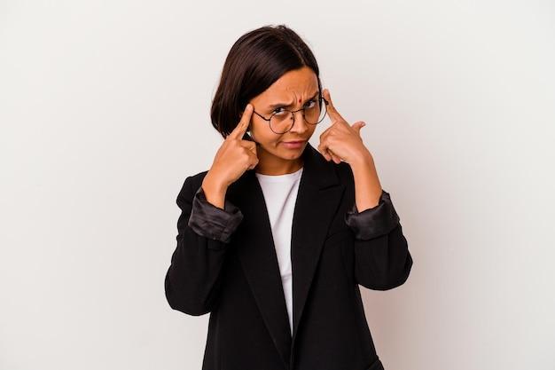 Jeune femme indienne d'affaires isolée sur blanc concentré sur une tâche, gardant l'index pointant la tête.