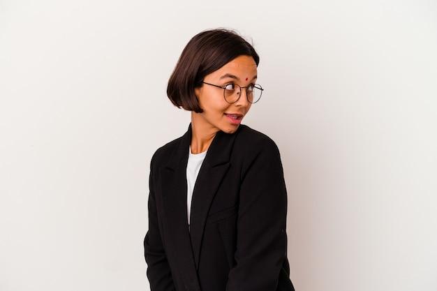 Jeune femme indienne d'affaires isolée sur fond blanc regarde de côté souriant, gai et agréable.