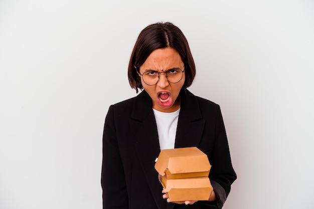 Jeune femme indienne d'affaires mangeant des hamburgers isolés criant très en colère et agressif.