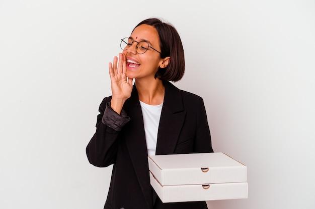 Jeune femme indienne d'affaires tenant des pizzas isolées criant et tenant la paume près de la bouche ouverte.