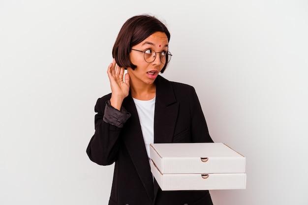Jeune femme indienne d'affaires tenant des pizzas isolées essayant d'écouter un potin.