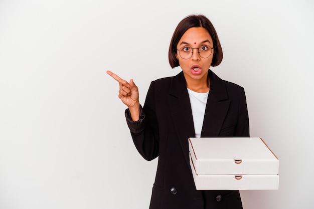 Jeune femme indienne d'affaires tenant des pizzas isolées pointant vers le côté