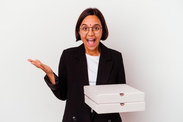 Jeune femme indienne d'affaires tenant des pizzas isolées recevant une agréable surprise, excitée et levant les mains.