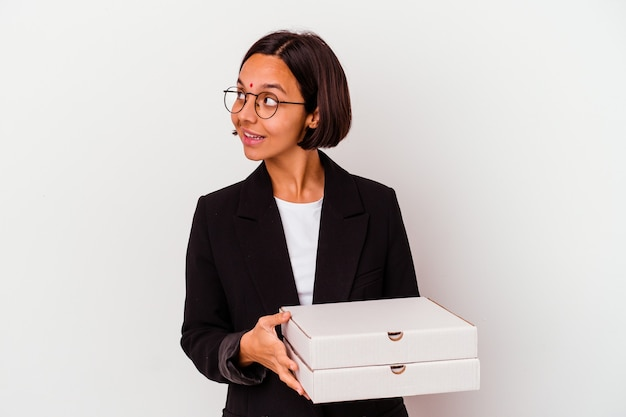 Jeune femme indienne d'affaires tenant des pizzas isolées regarde de côté souriant, gai et agréable.