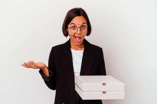 Jeune femme indienne d'affaires tenant des pizzas isolées surpris et choqués.