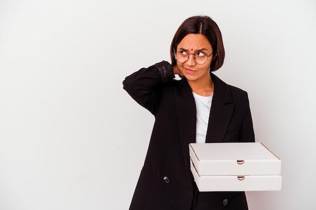 Jeune femme indienne d'affaires tenant des pizzas isolées touchant l'arrière de la tête, en pensant et en faisant un choix.