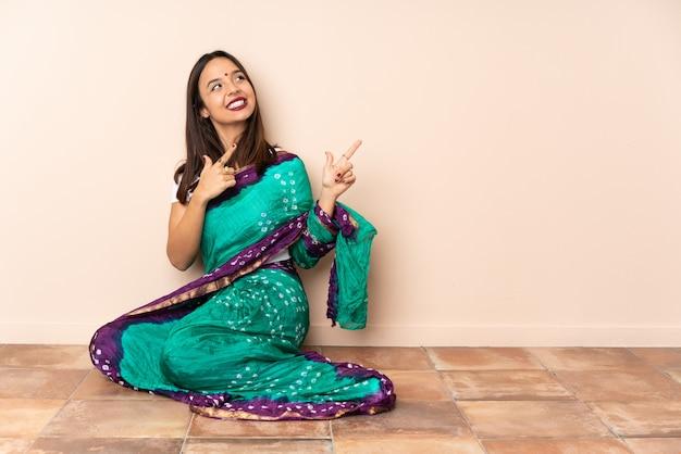 Jeune femme indienne assise sur le sol en pointant avec l'index une excellente idée