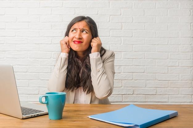 Jeune femme indienne au bureau couvrant les oreilles avec les mains, en colère et fatiguée d'entendre du son