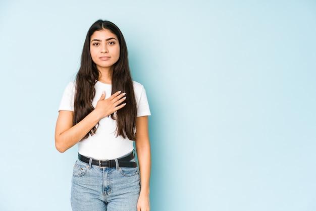 Jeune femme indienne sur bleu en prêtant serment, mettant la main sur la poitrine.