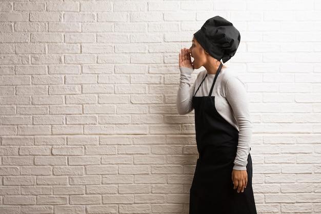 Jeune femme indienne de boulanger contre un mur de briques hurlant de colère