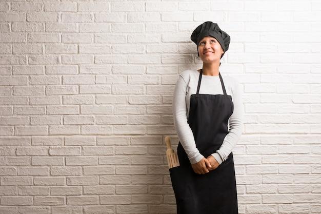 Jeune femme indienne de boulanger contre un mur de briques en levant