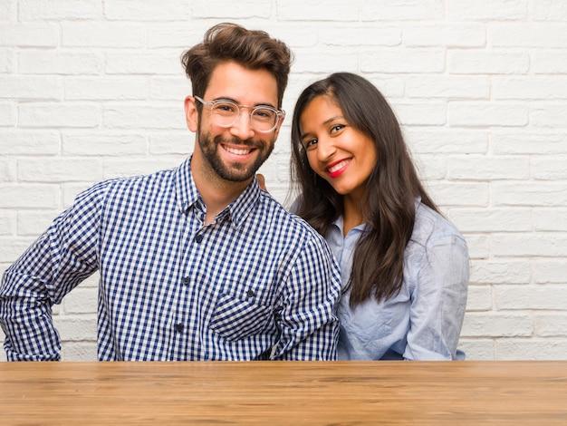 Jeune, femme indienne, et, caucasien, couple homme, à, mains hanches, debout, détendu et souriant, très positif et gai