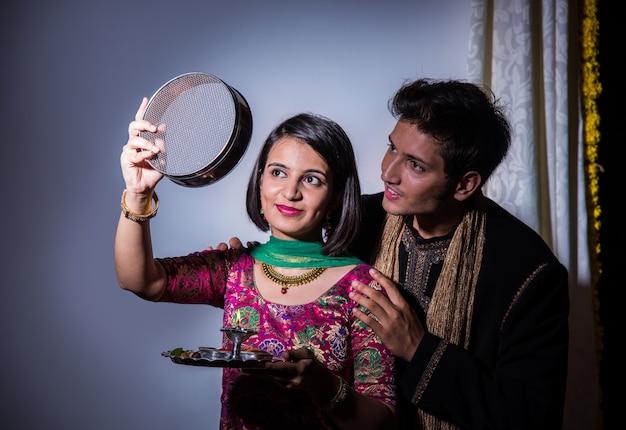 Jeune femme indienne célébrant le festival karwa chauth avec son mari