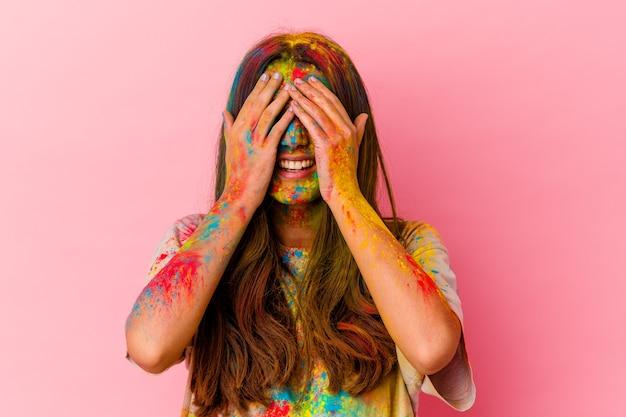 Jeune femme indienne célébrant le festival sacré isolé sur blanc couvre les yeux avec les mains, sourit largement en attente d'une surprise.