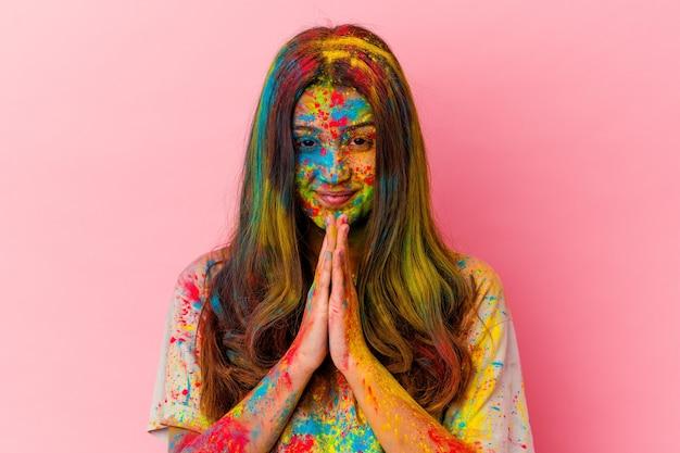 Jeune femme indienne célébrant le festival sacré isolé sur blanc tenant par la main en priant près de la bouche, se sent confiant.