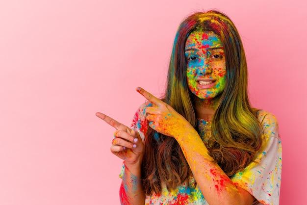 Jeune femme indienne célébrant la fête sacrée isolée sur blanc choqué pointant avec l'index vers un espace de copie.