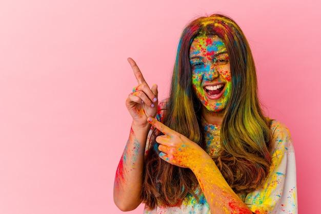 Jeune femme indienne célébrant la fête sacrée isolée sur blanc pointant avec l'index vers un espace de copie, exprimant l'excitation et le désir.