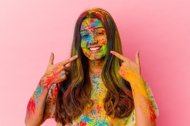 Jeune femme indienne célébrant la fête sacrée isolée sur des sourires blancs, pointant du doigt la bouche.
