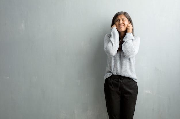 Jeune femme indienne contre un mur de grunge couvrant les oreilles avec les mains