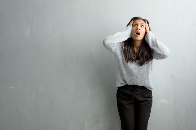 Jeune femme indienne contre un mur de grunge frustrée et désespérée, en colère et triste avec les mains sur la tête