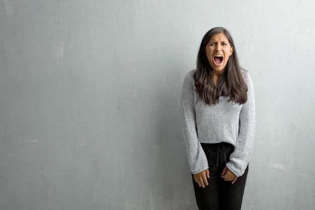 Jeune femme indienne contre un mur de grunge hurlant de colère
