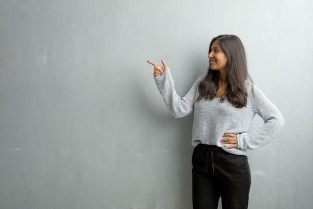 Jeune femme indienne contre un mur de grunge pointant vers le côté