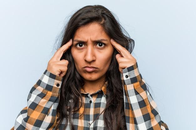 Jeune femme indienne cool concentrée sur une tâche, le maintenant les index pointés vers la tête