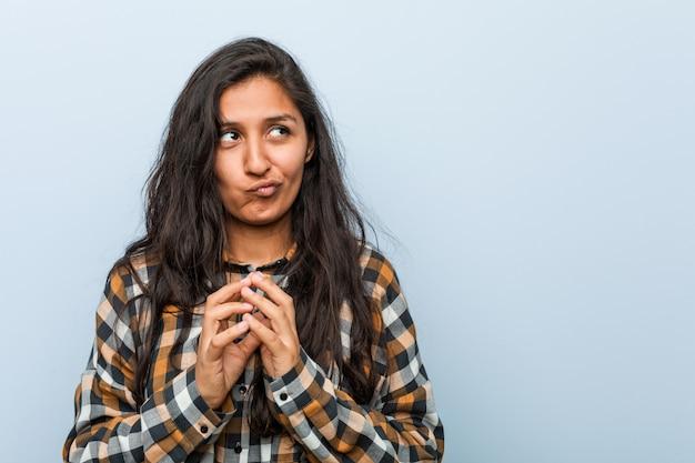 Jeune femme indienne cool faisant plan à l'esprit, mettant en place une idée.