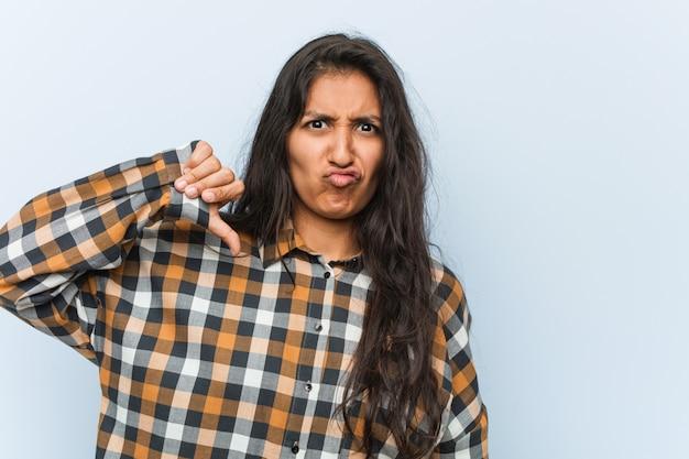 Jeune femme indienne cool montrant un geste d'aversion, les pouces vers le bas. notion de désaccord.