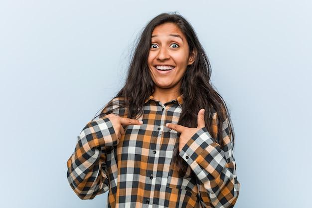 Jeune femme indienne cool surprise se montrant du doigt, souriant largement.